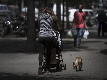 A woman walks her baby in Barcelona.