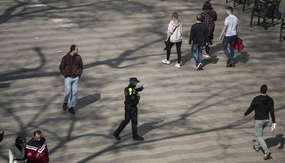 A police officer tells passers-by on La Rambla, Barcelona to clear the streets.