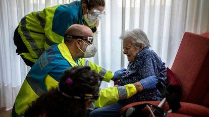 Health workers help an elderly patient in Madrid.
