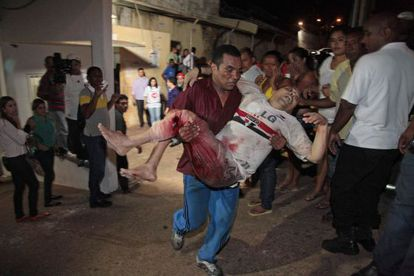 A prisoner from the Pedrinhas prison is carried to receive medical help after he was injured during a fight between rival gangs inside the jail on January 8.