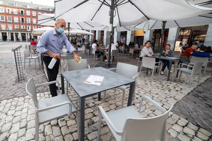 A waiter disinfects a table at a sidewalk café in Madrid.