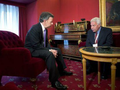 Colombian President Juan Manuel Santos speaks with former Spanish Prime Minister Felipe González on Monday in Madrid.