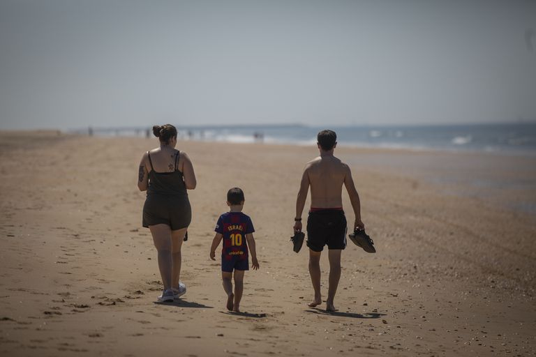 A family walks along Punta Umbría beach in Huelva province last Thursday.