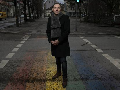 Vladimir Simonko, co-founder of the Lithuanian Gay League (LGL), stands on top of a pride flag painted with the help of volunteers.