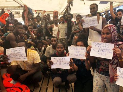 The rescued migrants hod up signs calling for help.