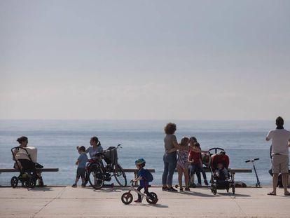 Families enjoy the seaside promenade in Barcelona.