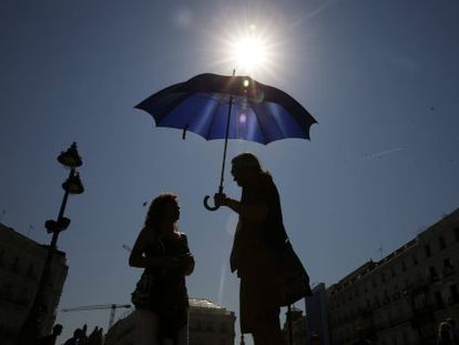Tourists protect themselves from the heat in Puerta del Sol in downtown Madrid.