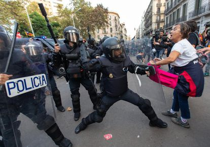Police officers try to disperse hundreds of protesters in Urquinaona square in Barcelona on Saturday.