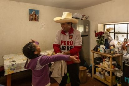 Pedro Castillo inside the kitchen of his house in Chugur with his nine-year-old daugther Alondra.