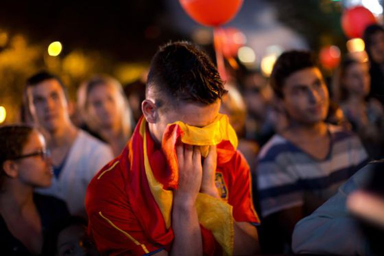 A man covers his face with a Spanish flag in Madrid's Puerta de Alcalá on Saturday night, after hearing the news that the city's bid to host the 2020 Olympics had failed.