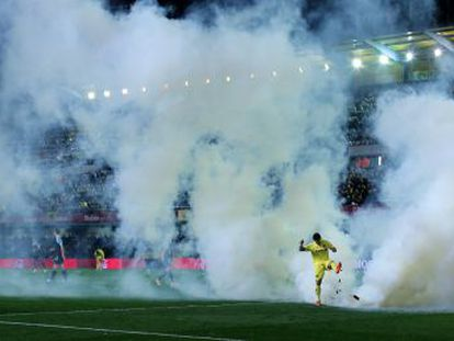Villarreal' s forward Jonathan Pereira kicks the teargas cannister thrown onto the field during the match against Villarreal.
