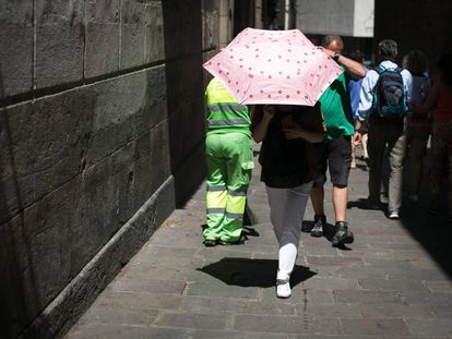 A woman in Barcelona uses an umbrella to protect herself from the sun.