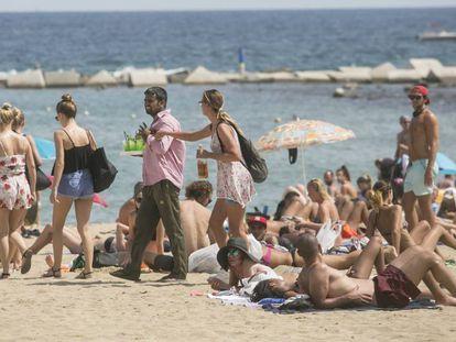 A plain clothes police officer stops a vendor on the Barceloneta beach on Wednesday.