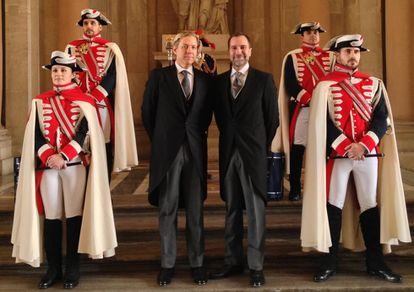 Costos with his husband Michael Smith, posing with a posse of halberdiers at the Royal Palace in Madrid.