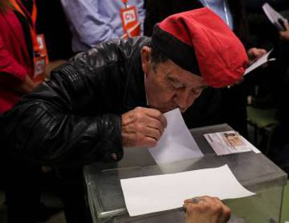 A man wearing a 'barretina', the traditional Catalan hat, kisses his ballot while voting in Catalonia's regional elections at a polling station in Barcelona