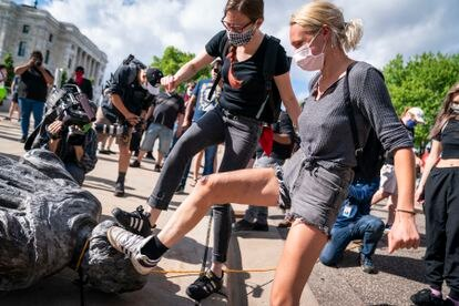 Protesters kicking a toppled Columbus statue in St. Paul, Minnesota, in June 2020.