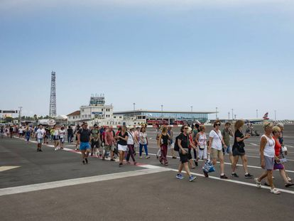 People cross a runway into Gibraltar.