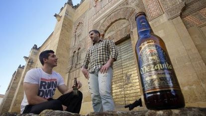 Two people drink Mezquita beer in front of the Córdoba monument.