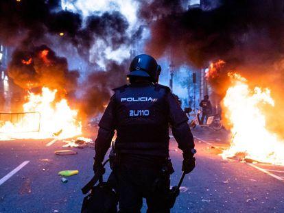 Un policía camina por via Laietana entre barricadas ardiendo.