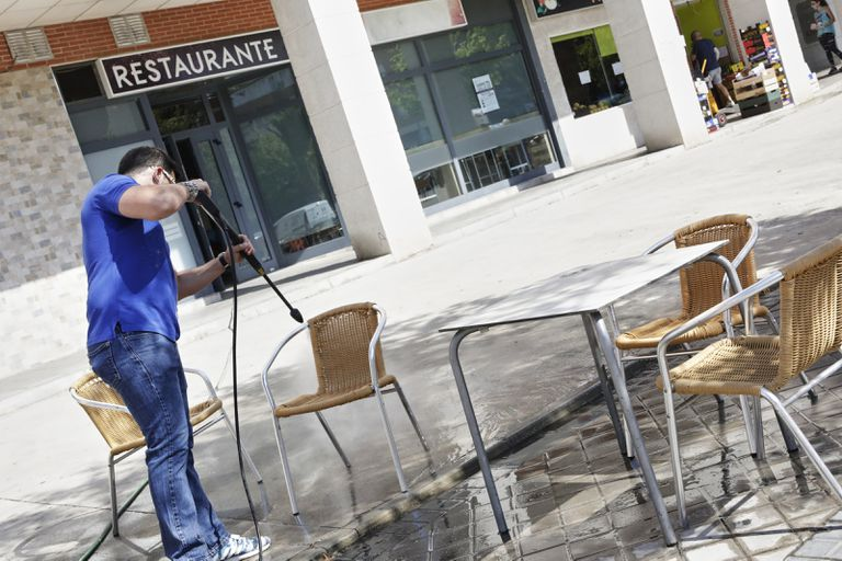 A restaurant worker in Madrid disinfects tables and chairs, ahead of the reopening of street cafés in the region on Monday.