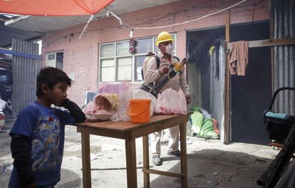 A sanitation worker fumigating a home in Oaxaca, Mexico.