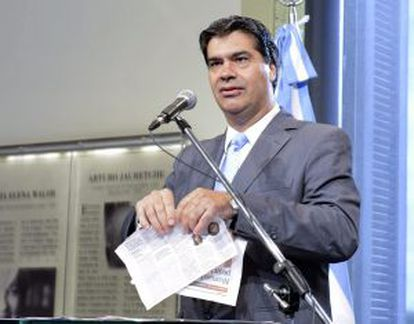 Cabinet chief Jorge Capitanich tears up a copy of 'Clarín' newspaper on Monday.