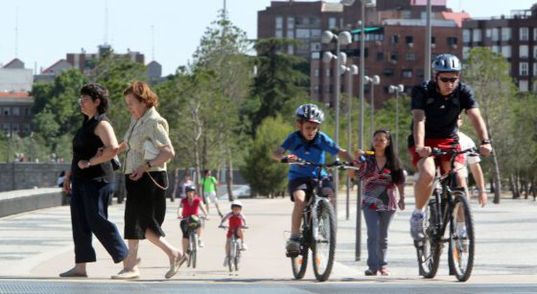Cyclists mingle with pedestrians in the Madrid Río park in the capital. But should all bike users have to wear helmets?