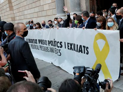 Catalan premier Quim Torra (c) outside the regional parliament with a banner in support of jailed separatist leaders on Monday.
