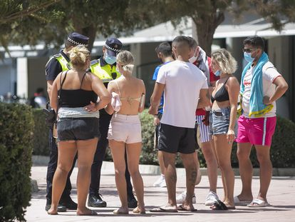 Two police officers in Málaga check that the mandatory use of face masks in public spaces is being followed.