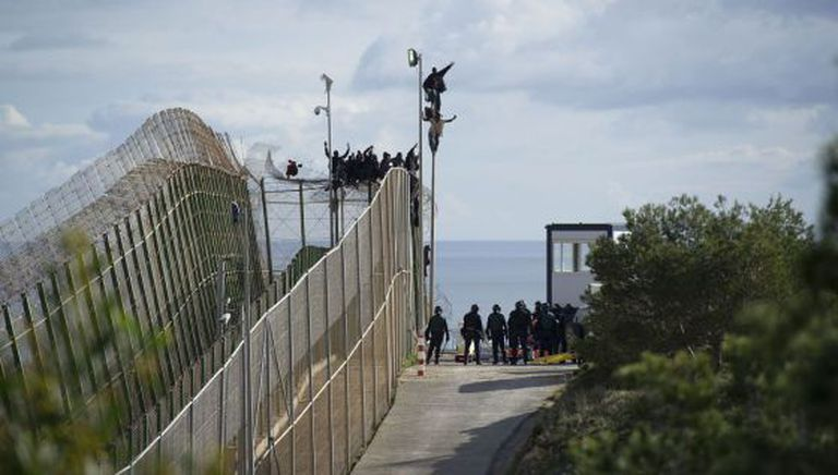 The would-be immigrants were perched on top of the border fence at Melilla for six hours on Thursday.