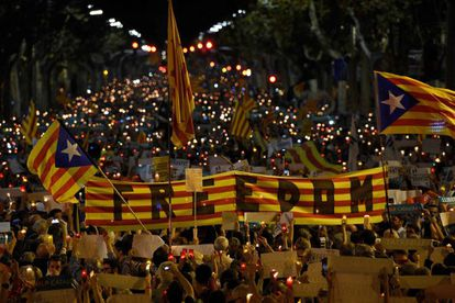 People hold a Catalan flag during candle-lit demonstration in Barcelona on October 17, 2017.