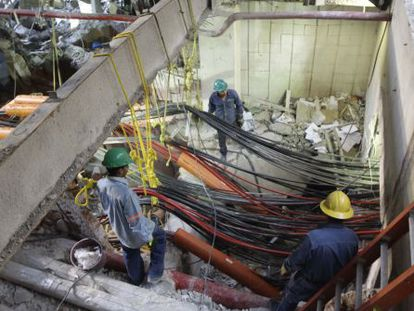 Workers sift through the blast site on Tuesday.