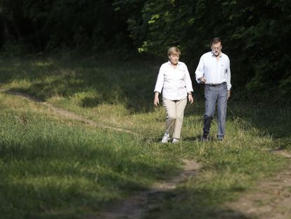 Angel Merkel and Mariano Rajoy take a walk in Meseberg, Germany last August.