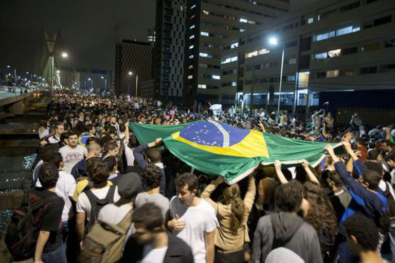 Students lift a Brazilian flag during Monday night's protest in São Paulo.