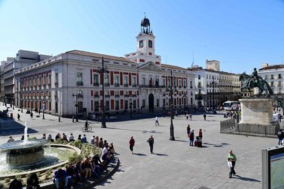 Several people walk through the usually crowded Puerta del Sol in central Madrid on March 14 after regional authorities ordered all stores in the region to be closed.