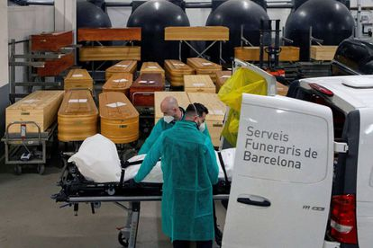 Funeral workers transferring the remains of a Covid-19 victim in Barcelona.
