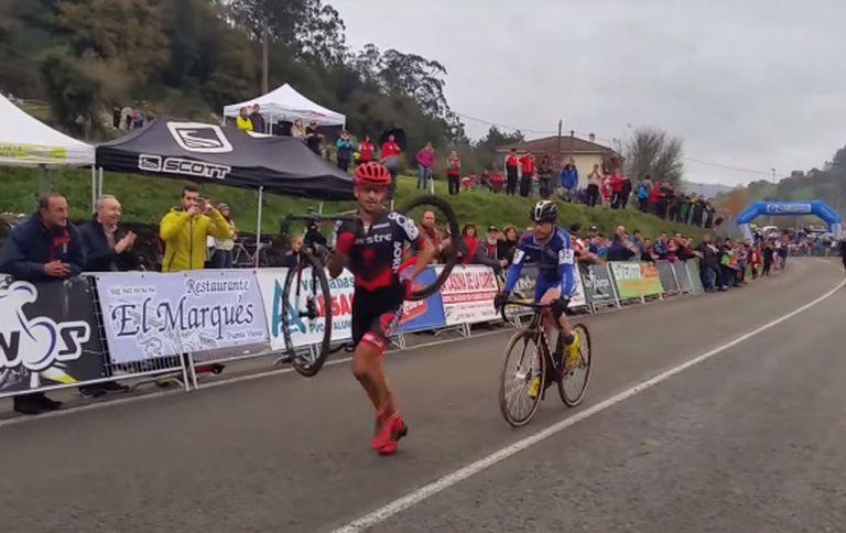 Ismael Esteban carries his bike as opponent Agustín Navarro follows.
