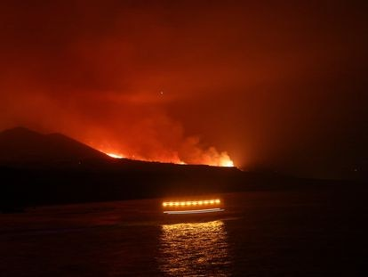 Coastguards pass as lava is seen arriving at the sea following the eruption of a volcano, seen from the Port of Tazacorte, on the Canary Island of La Palma, Spain, September 28, 2021. REUTERS/Nacho Doce