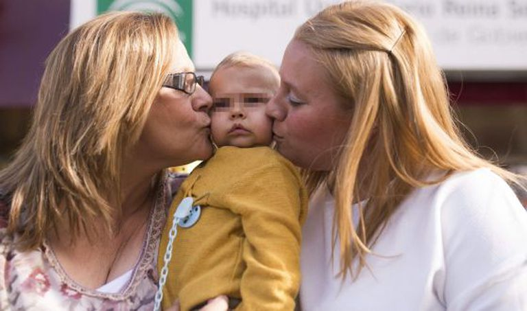 Francisca Fuentes (left), her grandson Juan José and the baby's mother outside the Córdoba hospital where the surgery took place.