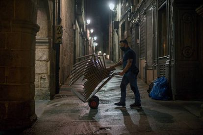 A worker put away chairs in Mayor square in Ourense on Sunday night, when the curfew came into effect.