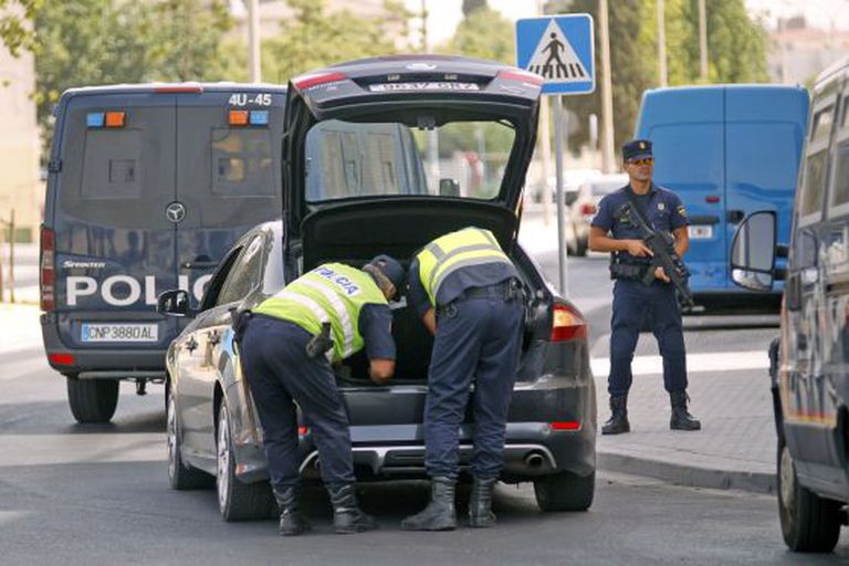 Police search a vehicle in the Tres Mil Viviendas area of Seville Friday.
