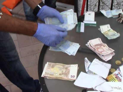 A Civil Guard officer counts the money seized from the drug ring.