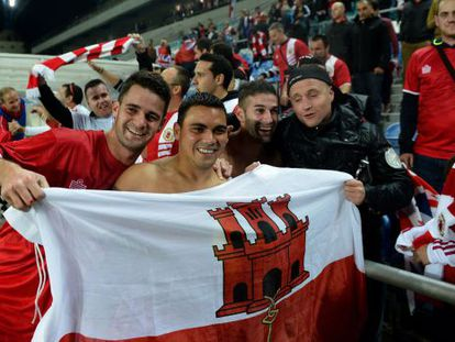 Gibraltar midfielder Robert Guilling (second left) and teammates celebrate with supporters after holding Slovakia in Portugal.