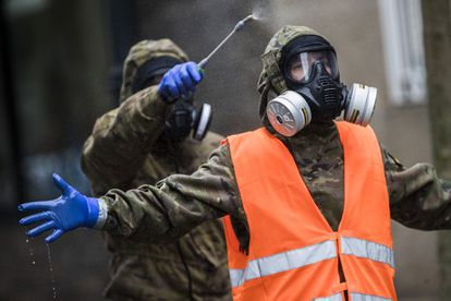 Members of Spain's Emergency Military Unit disinfect one another after disinfecting a seniors' home in Vigo in a file photo from April 2020.