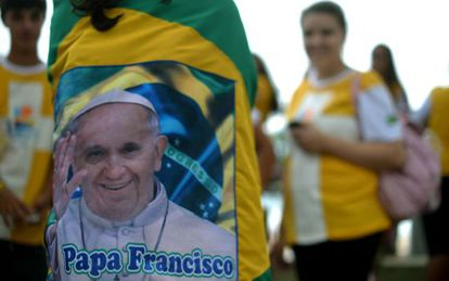 A young pilgrim wrapped in a Brazilian flag with an image of Pope Francis speaks with mates in Rio de Janeiro.