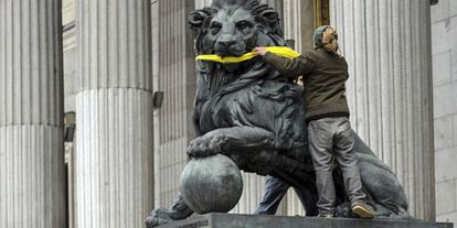 A Greenpeace activist gags one one the stone lions presiding the Spanish Congress to protest the Citizen Safety Law.