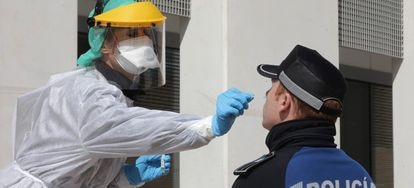 A medical biologist handles a swab to test a police officer at Casa de Campo in Madrid in March.