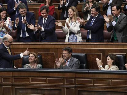 Deputies with Spain's ruling Popular Party applaud following the budget vote.