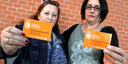 Two residents of Fuenlabrada hold up the social services card that is offered to undocumented migrants in their city.