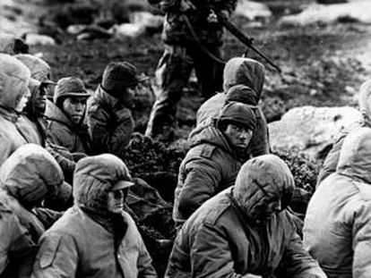 A Royal Navy officer guards Argentinean prisoners during the 1982 Falklands War.